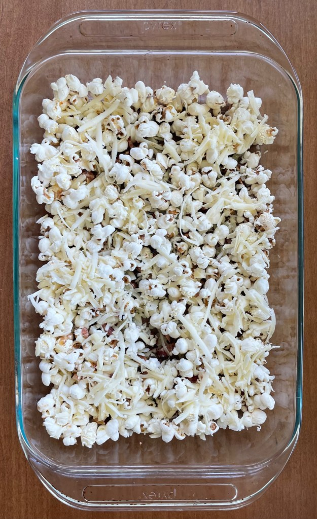 a baking pan of unbaked bacon cheddar popcorn
