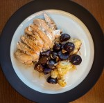 a plate of chicken and roasted purple potatoes and cauliflower