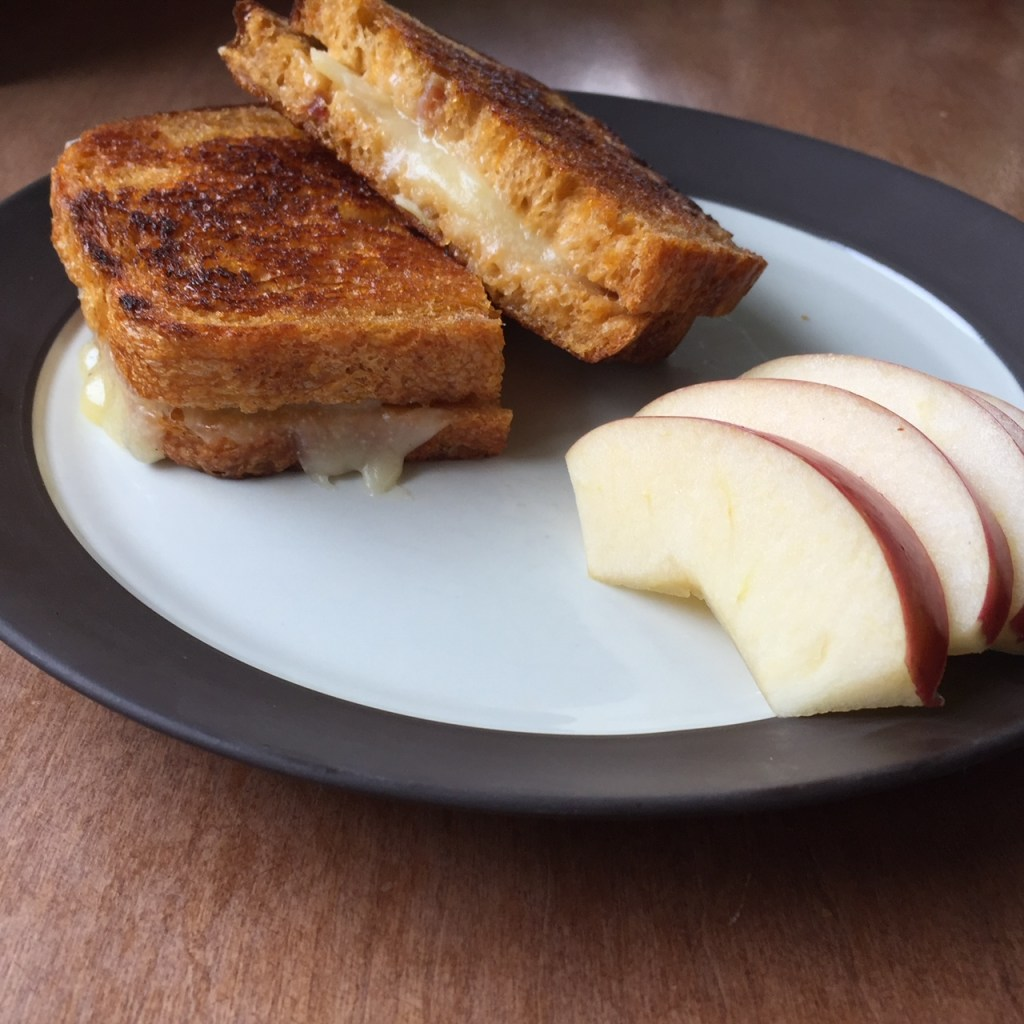 a grilled cheese and apple sandwich on a plate with a few apple slices