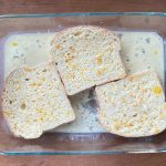 a dish of three slices of bread soaking up the orange zest French toast mixture
