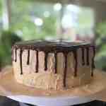 a peanut butter chocolate ganache drip cake on a cake stand