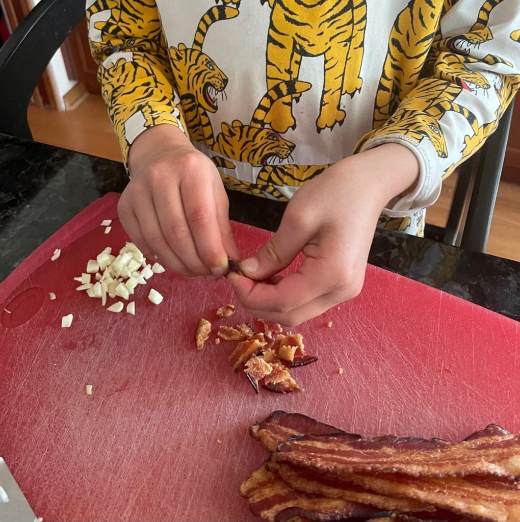 A child ripping apart strips of cooked bacon