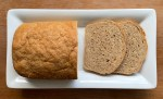 a loaf of honey wheat bread and two slices on a plate
