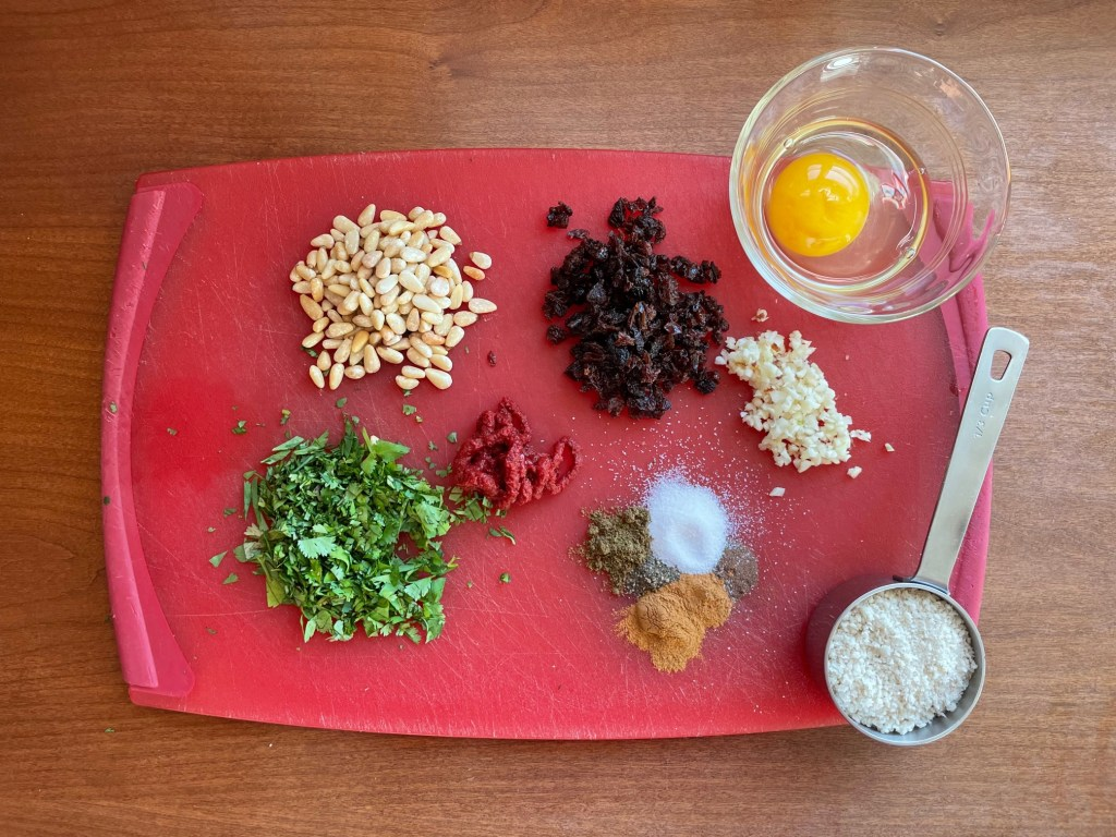 ingredients for lamb meatballs with pine nuts and raisins plus chopped cilantro, tomato paste, spices, chopped garlic, an egg in a small glass bowl, and a measuring cup with panko