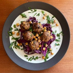 a plate of lamb meatballs with pine nuts and raisins atop fried chickpeas and sliced purple cabbage with a chopped parsley garnish
