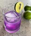 a purple lavender gimlet in a lowball glass garnished with a lime circle and lavender sprig