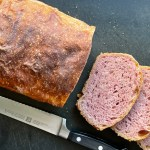 a loaf of pink-tinked purple sweet potato sourdough with three slices and a bread knife