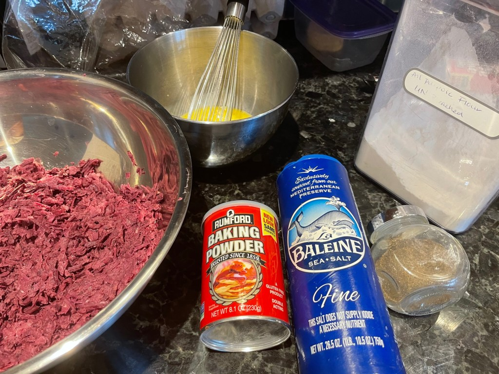 ingredients for purple sweet potato pancakes including grated sweet potato and onion, baking powder, salt and pepper, flour, and beaten eggs in a bowl with a whisk