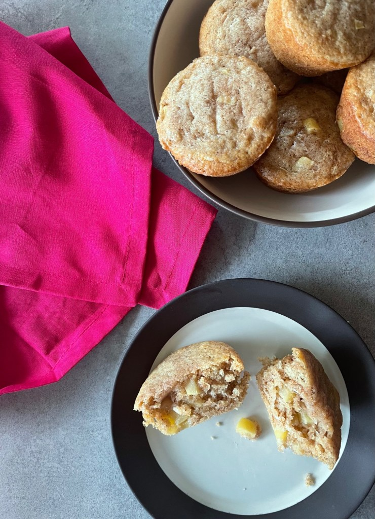 a plate with two halves of a muffin and a bowl of sourdough discard apple muffins alongside a red napkin