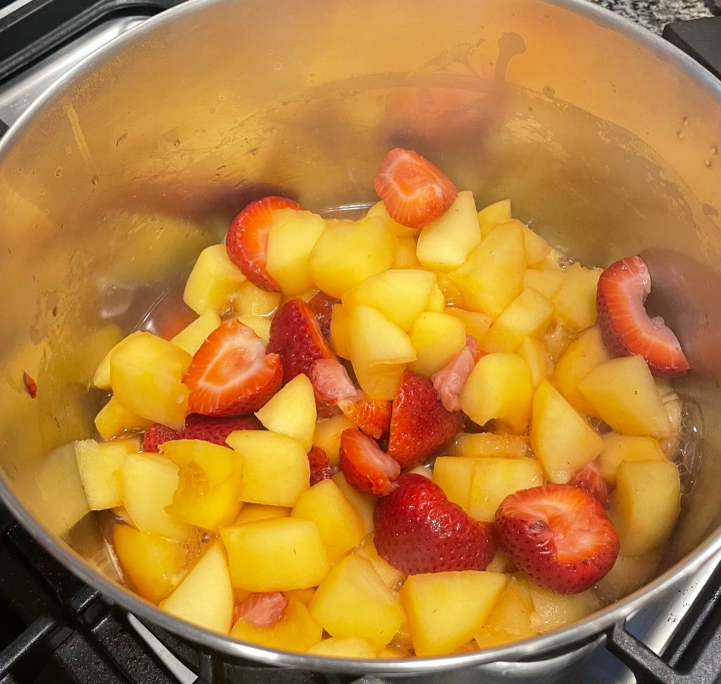 a pot containing apple and strawberry chunks