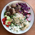 A bowl with lamb meatballs with cumin and coriander, Israeli couscous with lemon and mint, homemade hummus, feta cheese, a variety of vegetables, and garnished with pine nuts parsely and cilantro