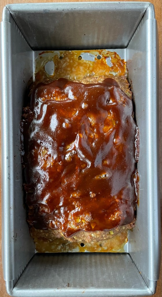A meatloaf pan with a meatloaf with a hoisin sauce glaze