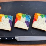 three slices of rainbow bread on a cutting board with a knife
