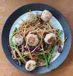 a plate of shrimp and pork meatballs over noodles and vegetables