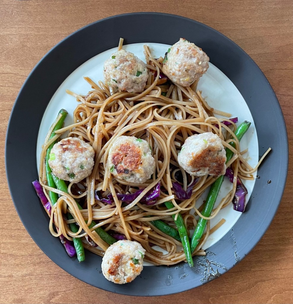 Shrimp and pork meatballs on a plate of noodles and vegetables
