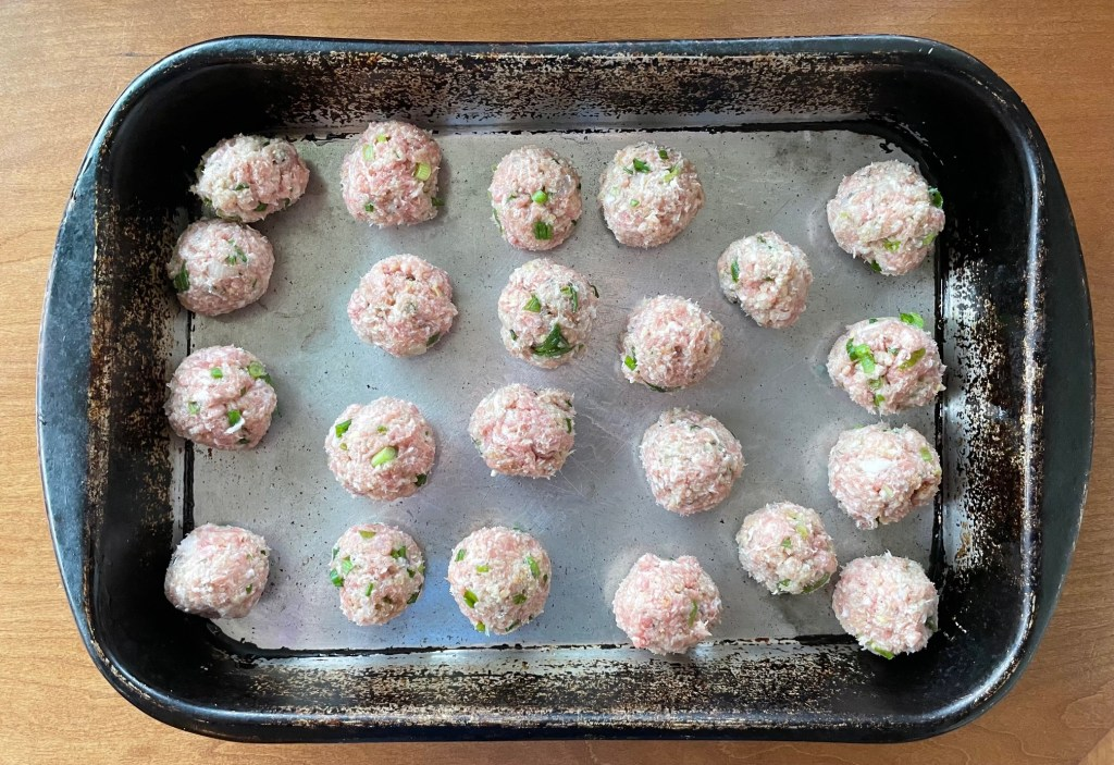 Unbaked shrimp and pork meatballs in a roasting pan