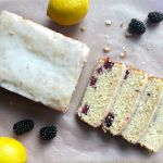 a loaf of blackberry lemon bread with four slices and surrounded by a few lemons and blackberries