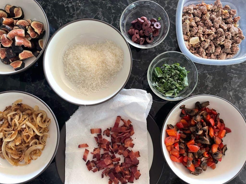 an image of pizza making mis-en-place with bowls of fresh figs, grated Parmesan, sliced olives, chopped basil, cooked sausage and fennel, caramelized onions, cooked bacon, and a bowl of cooked mushrooms and red peppers