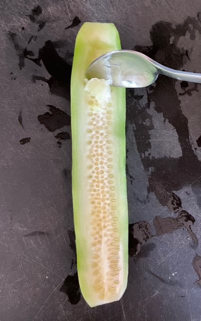A spoon removing the seeds from a cucumber cut in half