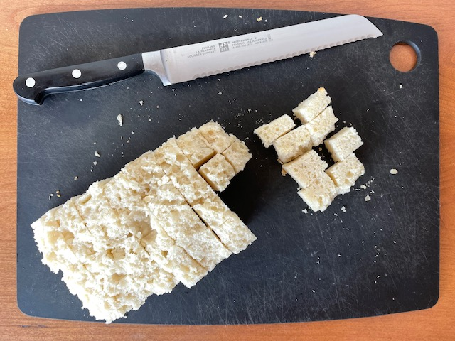A cutting board with a bread knife and a crustless loaf of bread cut into cubes.