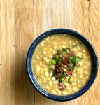 a bowl of sweet corn soup garnished with chopped bacon and green onions