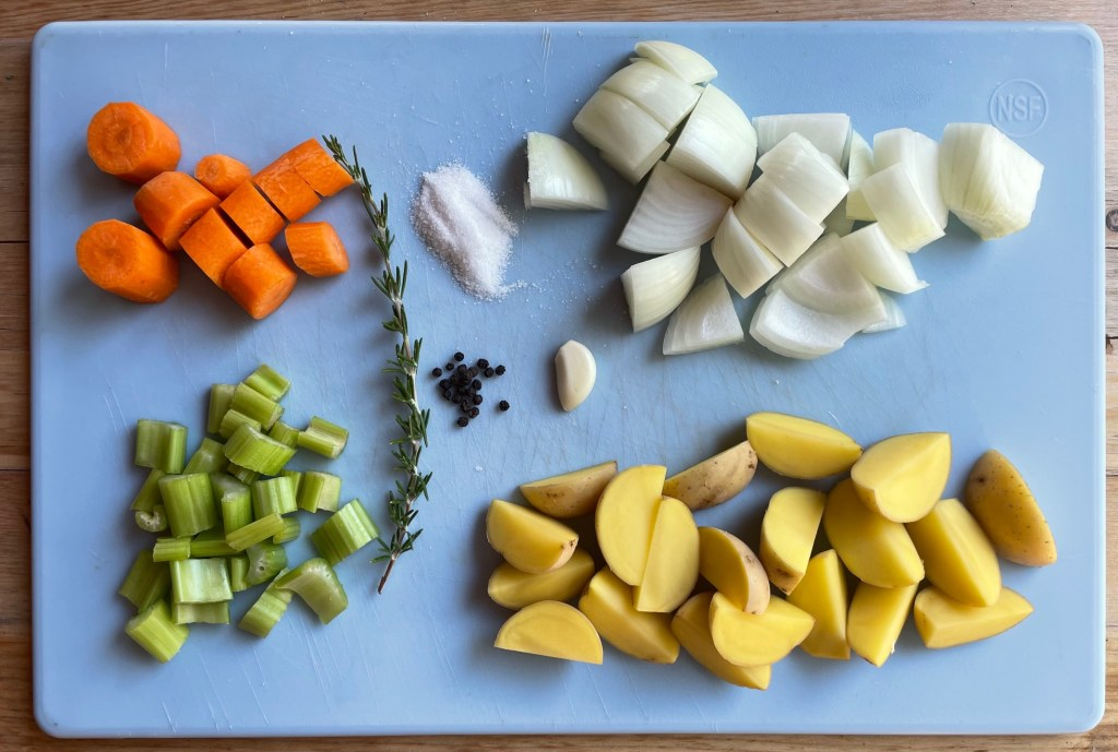 a cutting board with all of the ingredients for the corn broth