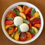 a peach and burrata caprese salad from above with sliced peaches, two different sliced tomatoes, whole basil leaves, and two balls of burrata