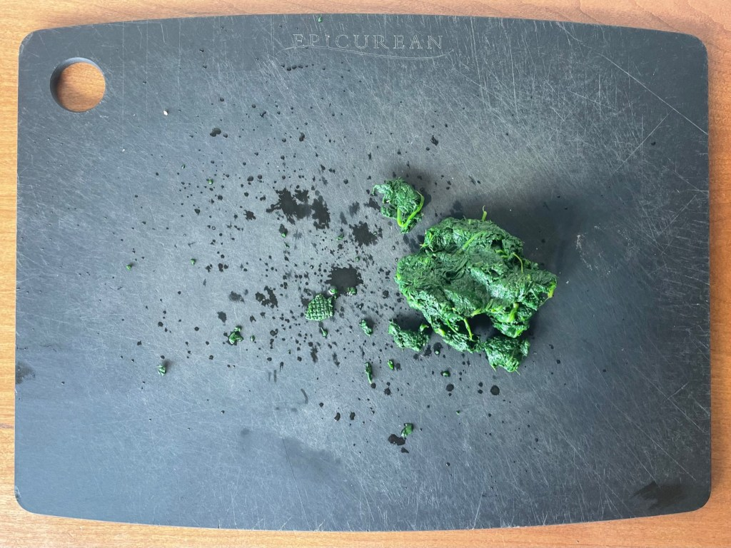 cooked spinach on a cutting board