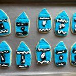 a tray of 10 crayon shaped cookies decorated with blue royal icing