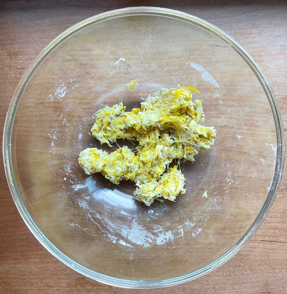 a bowl with grated squash and flour showing how the squash can be pulled apart to mix