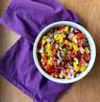 a bowl of mango pico de gallo on a purple cloth