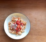a bowl of pink sauce pasta topped with sauteed tomatoes and Parmesan