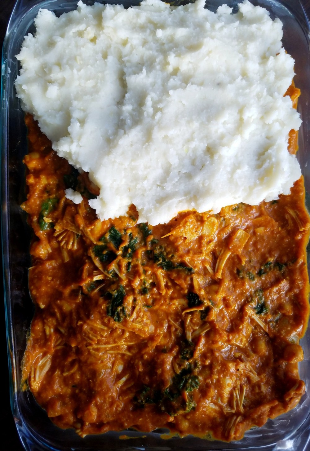 Madras curry spread in the bottom of a casserole dish and topped with savory coconut mashed potatoes