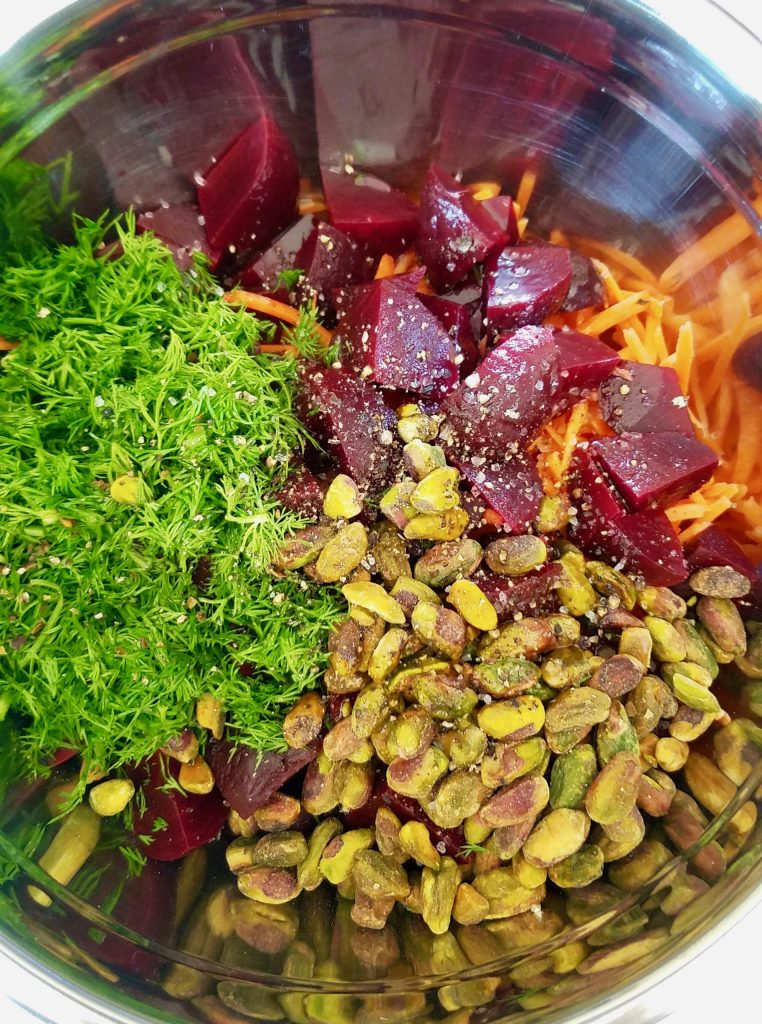 Mixing the ingredients for Carrot and Beet Salad with Fresh Dill and Roasted Pistachios