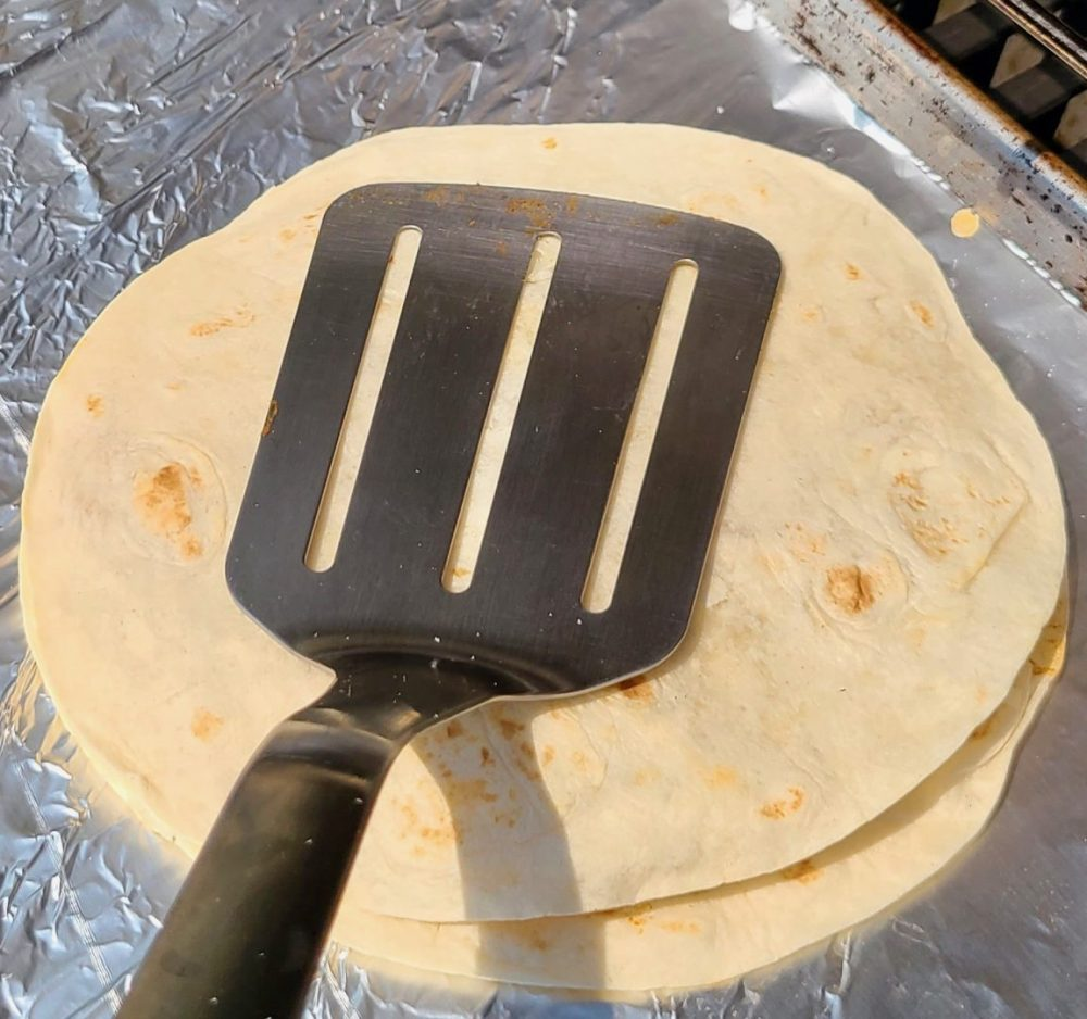 Spatula smashing tortillas together on a grill