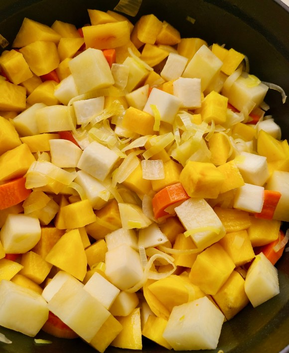 Potatoes, turnips, carrots, leeks, onions and golden beets in a pot