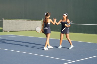 Doubles partners Anja Seng (Sr.) and Kayla Agustin (So.) high-five after a point. (Danya Clein)