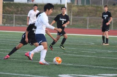 David Kim (Sr.) looks to pass past a Pacific defender. (Lexi Lim)