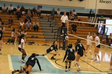 Kira Cashman (Sr.) lunges to save the ball, solidifying a win for UHS in the first set against CdM. (M.Olney)