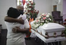In this July 21, 2020, file photo, Darryl Hutchinson, facing camera, is hugged by a relative during a funeral service for Lydia Nunez, who was Hutchinson's cousin at the Metropolitan Baptist Church in Los Angeles. Nunez died from COVID-19. Southern California funeral homes are turning away bereaved families because they're running out of space for the bodies piling up during an unrelenting coronavirus surge. (AP Photo/Marcio Jose Sanchez, File)