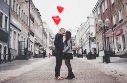 Koppel op straat met hartjes balonnen
