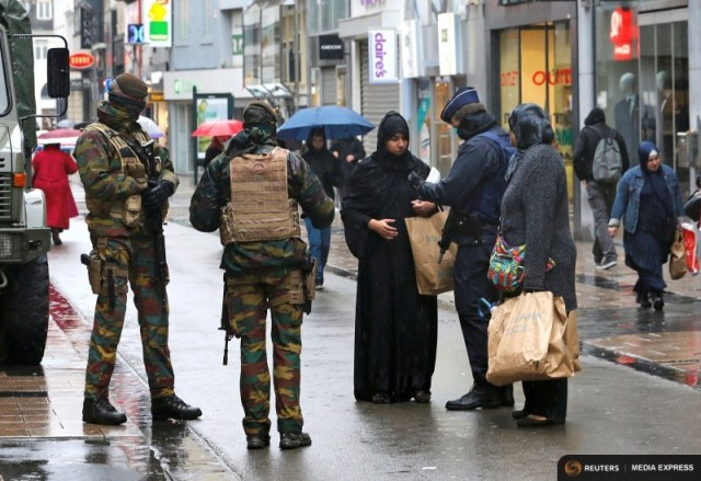 Belgian soldiers and a police officer control the documents of a woman in a shopping street in central Brussels, November 21, 2015, after security was tightened in Belgium following the fatal attacks in Paris.REUTERS/Youssef Boudlal