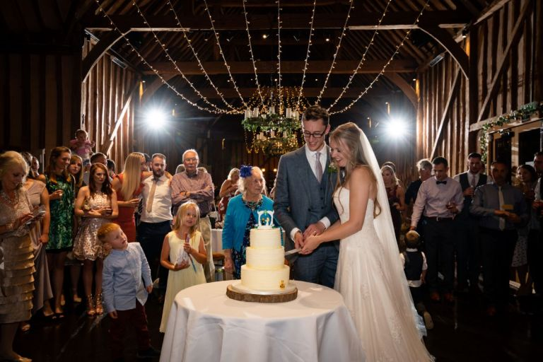 Jen and Joe cutting the cake at their barn wedding photographed by Andy Sidders.