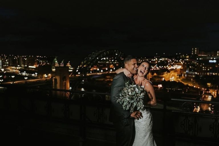 The happy couple in front of the beautiful city of Newcastle alight at night!
