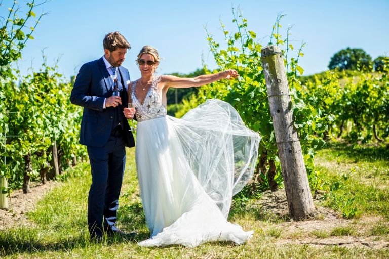 The bride and groom posing in the vineyard.