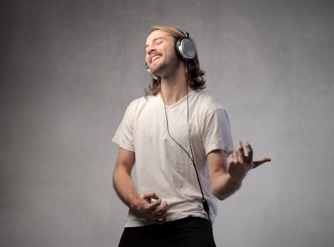 a guy playing air guitar with headphones on. wearing a white t-shirt