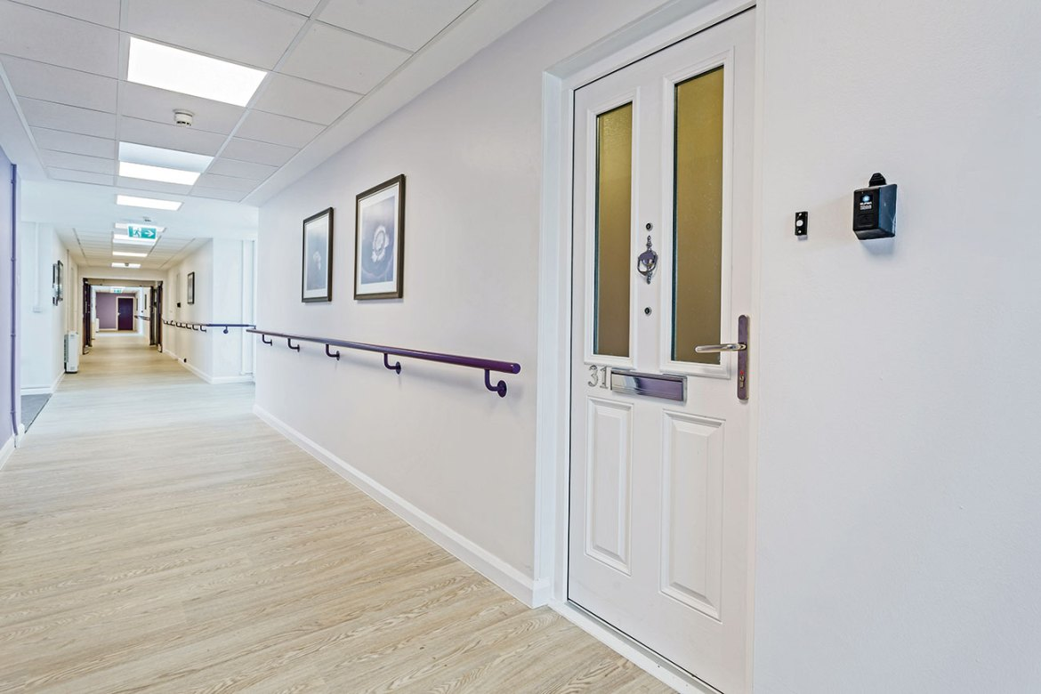 A glazed (Neuma fds 48P 9N) GRP composite fire entrance door in White, one of many door styles installed in a sheltered accommodation block in the west of England.