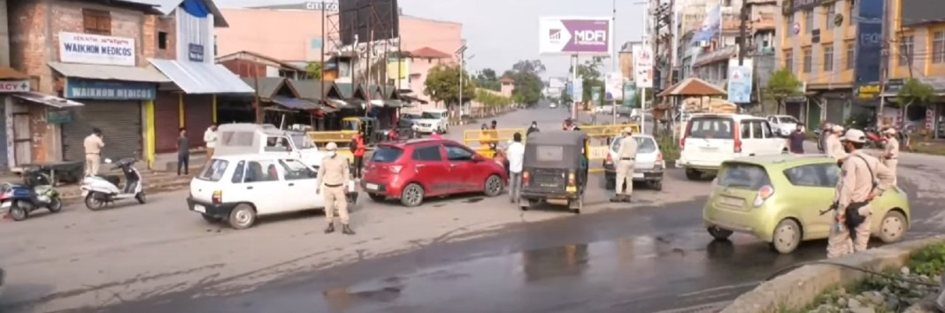 Police enforcing curfew at Palace Gate in Imphal East district on Tuesday