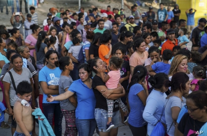 "In this Aug. 30, 2019, photo, migrants, many who were returned to Mexico under the Trump administration's ""Remain in Mexico,"" program wait in line to get a meal in an encampment near the Gateway International Bridge in Matamoros. Many shelters at…"