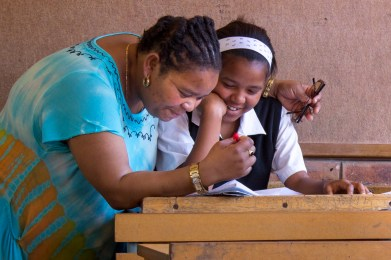 Landie Booi-Mngcambe assists Michaela Opperman with her English homework at Mary Waters Secondary School, Grahamstown on Wednesday, October 2, 2013. Landie enjoys teaching because she loves working with young people, ensuring a brighter future for the next generation. (Photo: Sarah Kingon)